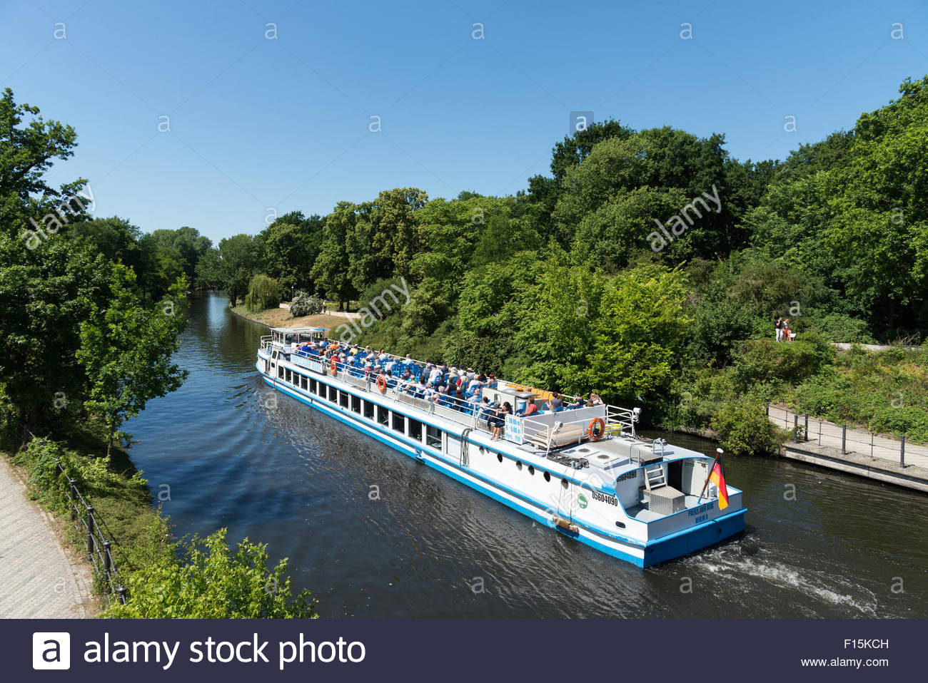 Tour boat travelling beside the Tiergarten along the Landwehr Canal, Berlin, Germany - Stock Image