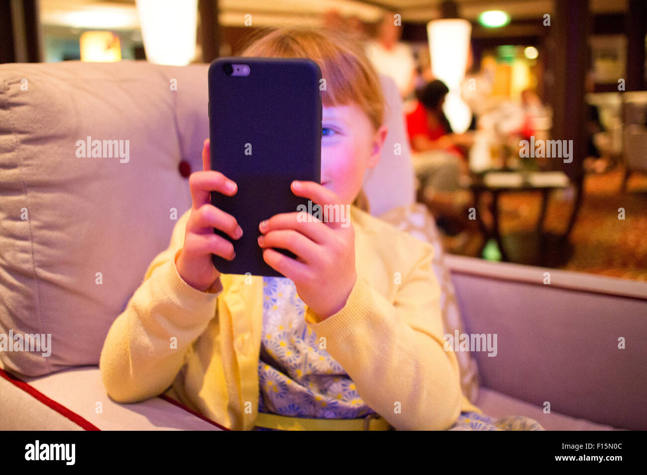 5 year old girl taking a photo with an iphone 6 plus - Stock Image