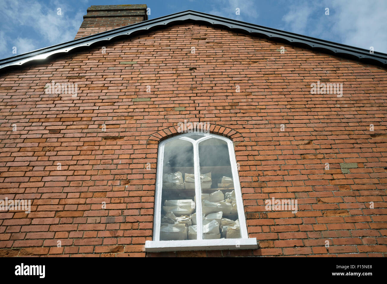 Papers stacked in the window of a business in Saxmundham, Suffolk, UK. - Stock Image