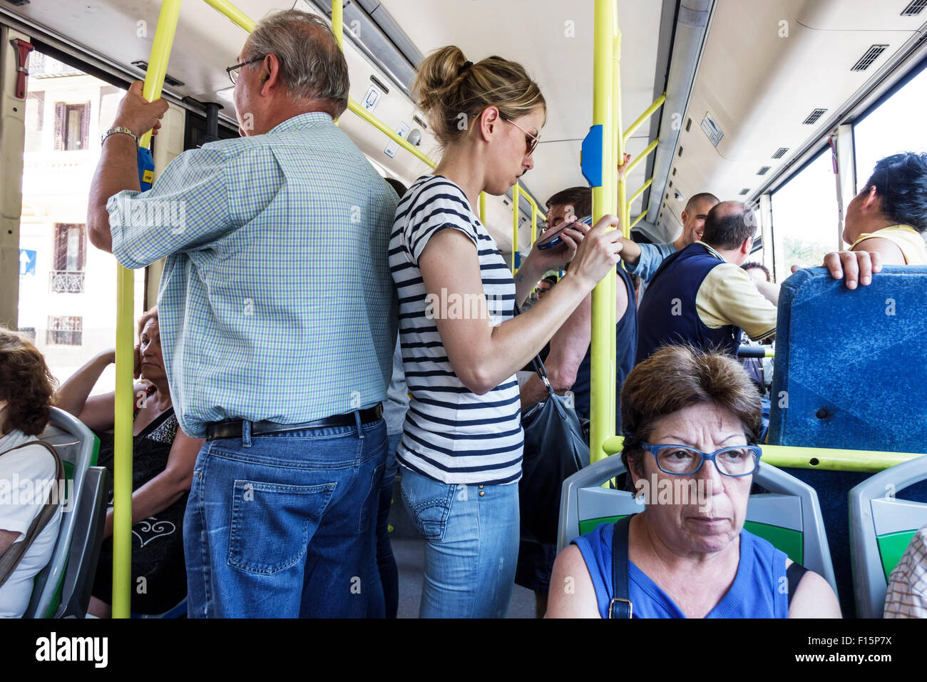Madrid Spain Europe Spanish Metro EMT bus public transportation riders passengers standing Hispanic man woman - Stock Image