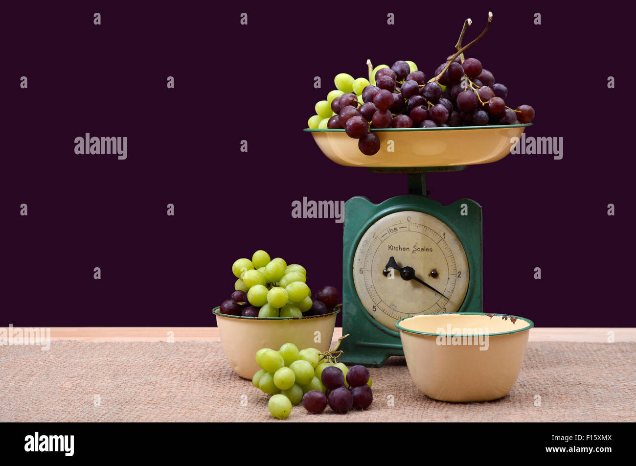 Weighing grapes on vintage scale with old enamel bowls on burlap covered pine table. - Stock Image