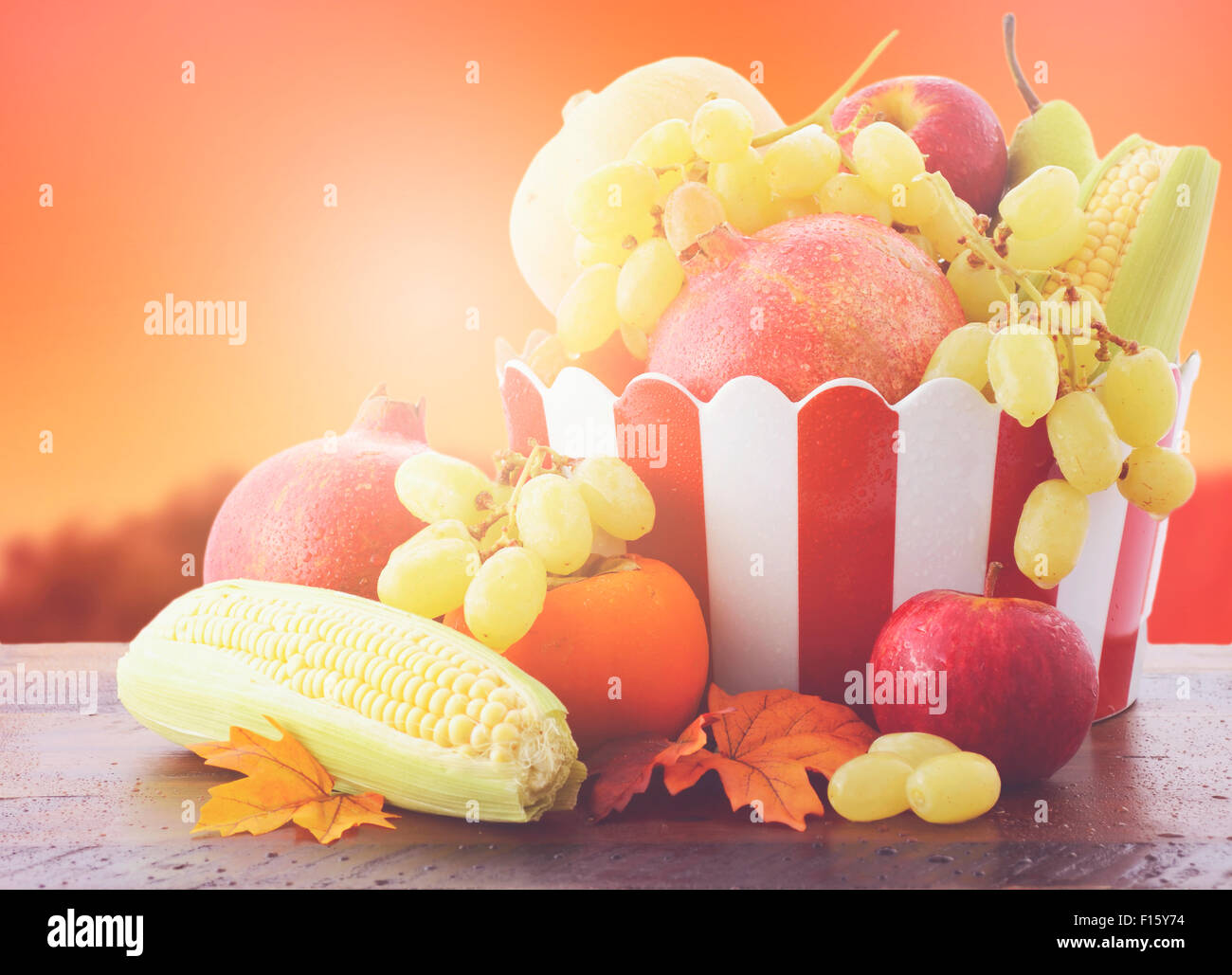 Bowl of Autumn fruit and vegetables on vintage wood table with Autumn sunset background, with added filters and - Stock Image