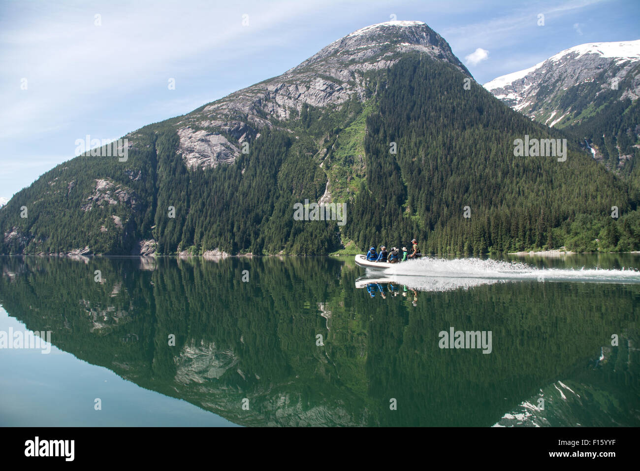 A wilderness guide and tourists travel up a remote lake by zodiac in the Great Bear Rainforest of British Columbia, - Stock Image