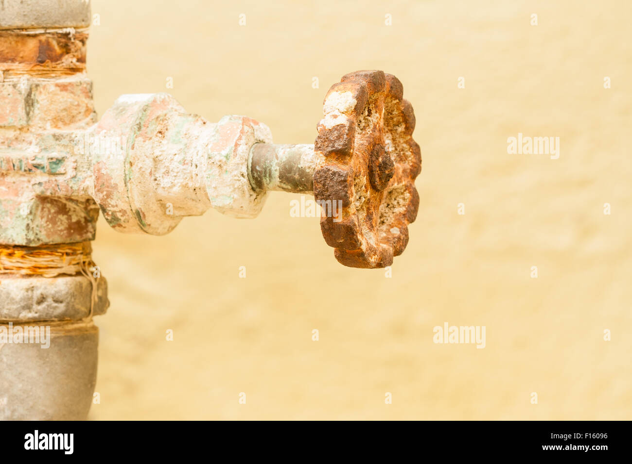 Closeup view of a gate valve that is covered with rust. - Stock Image