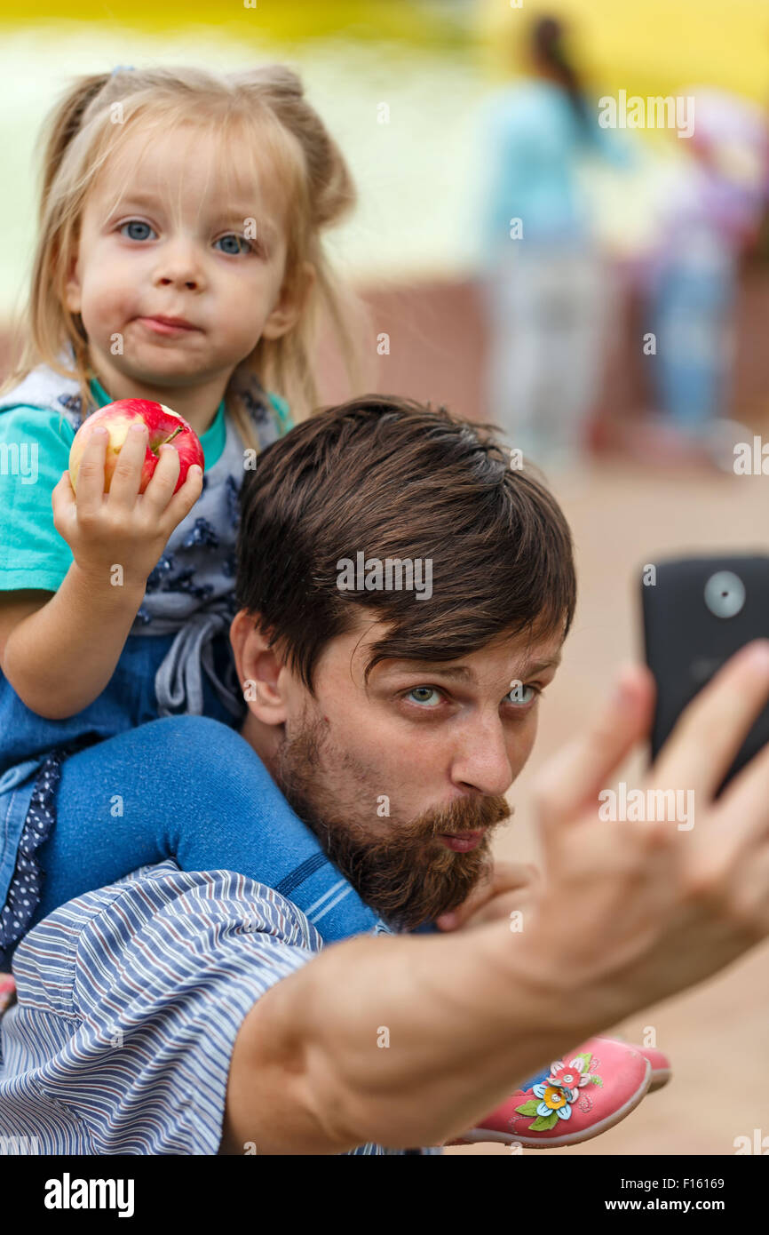 Father holds daughter piggyback and makes a cell phone self-portrait. Selfie. The concept of the modern family. - Stock Image