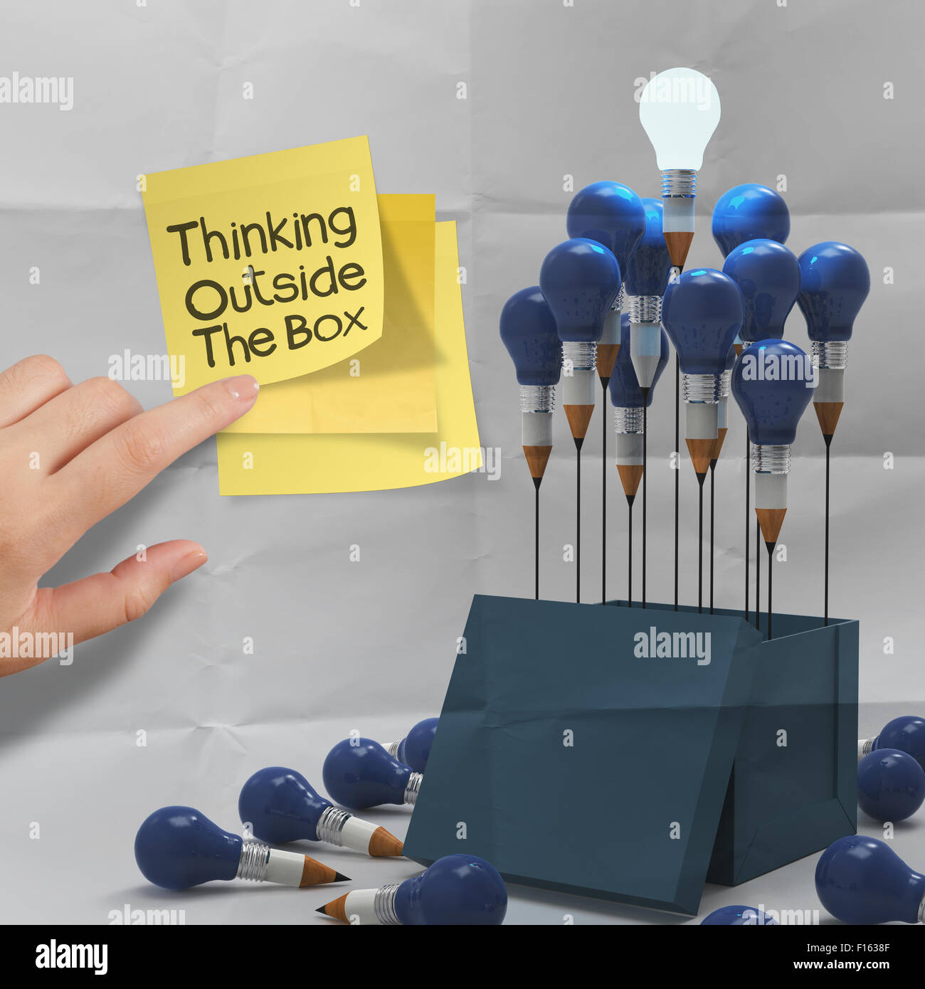 thinking outside the box on sticky note and pencil lightbilb as creative on crumpled paper - Stock Image