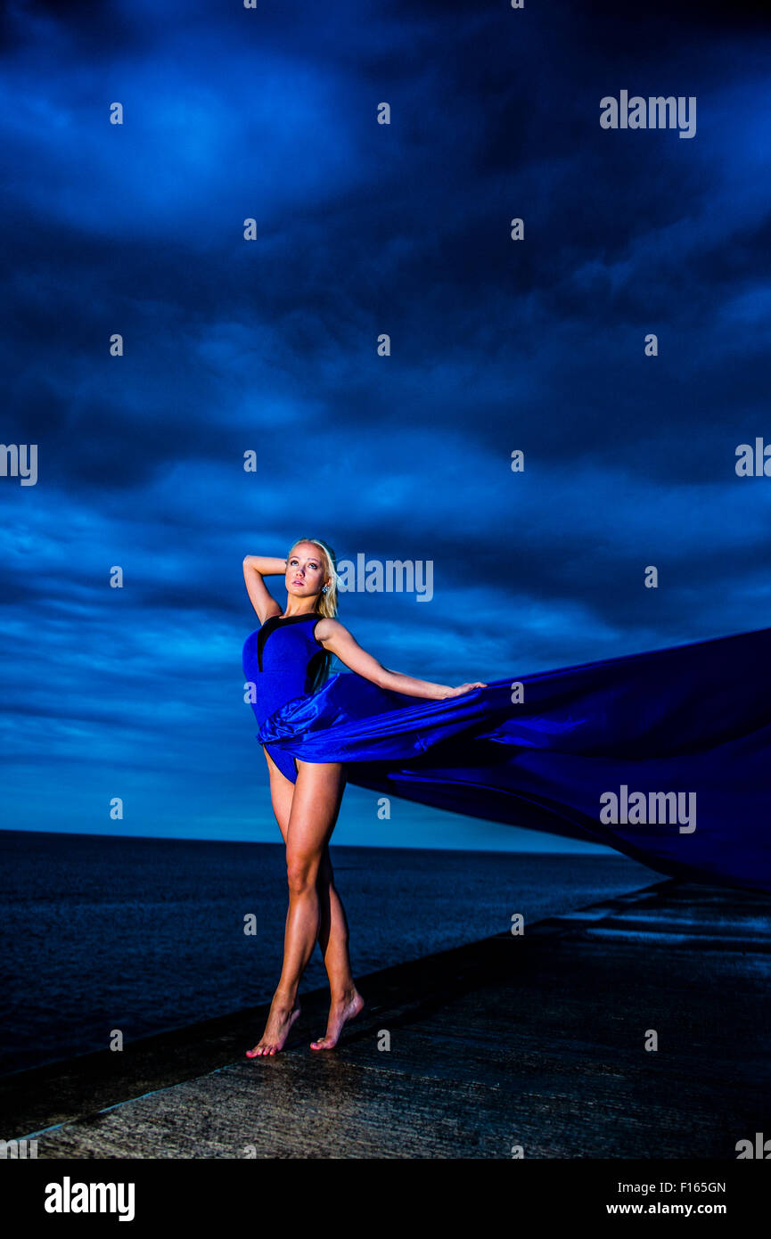 Outdoor location photography - A tall slim blond blonde woman girl model posing outdoors on a wet evening with a - Stock Image