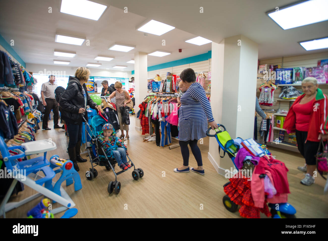 Women shoppers looking at bargain cheap kids clothes in a new branch of the  Barnardo s charity children s store in Aberystwyth Wales UK 5ed67e791