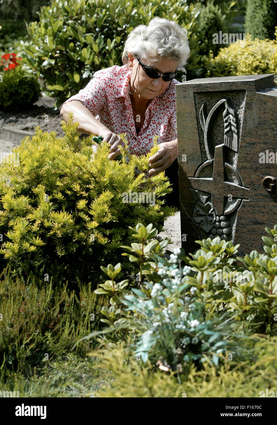 Woman maintains a grave Stock Photo