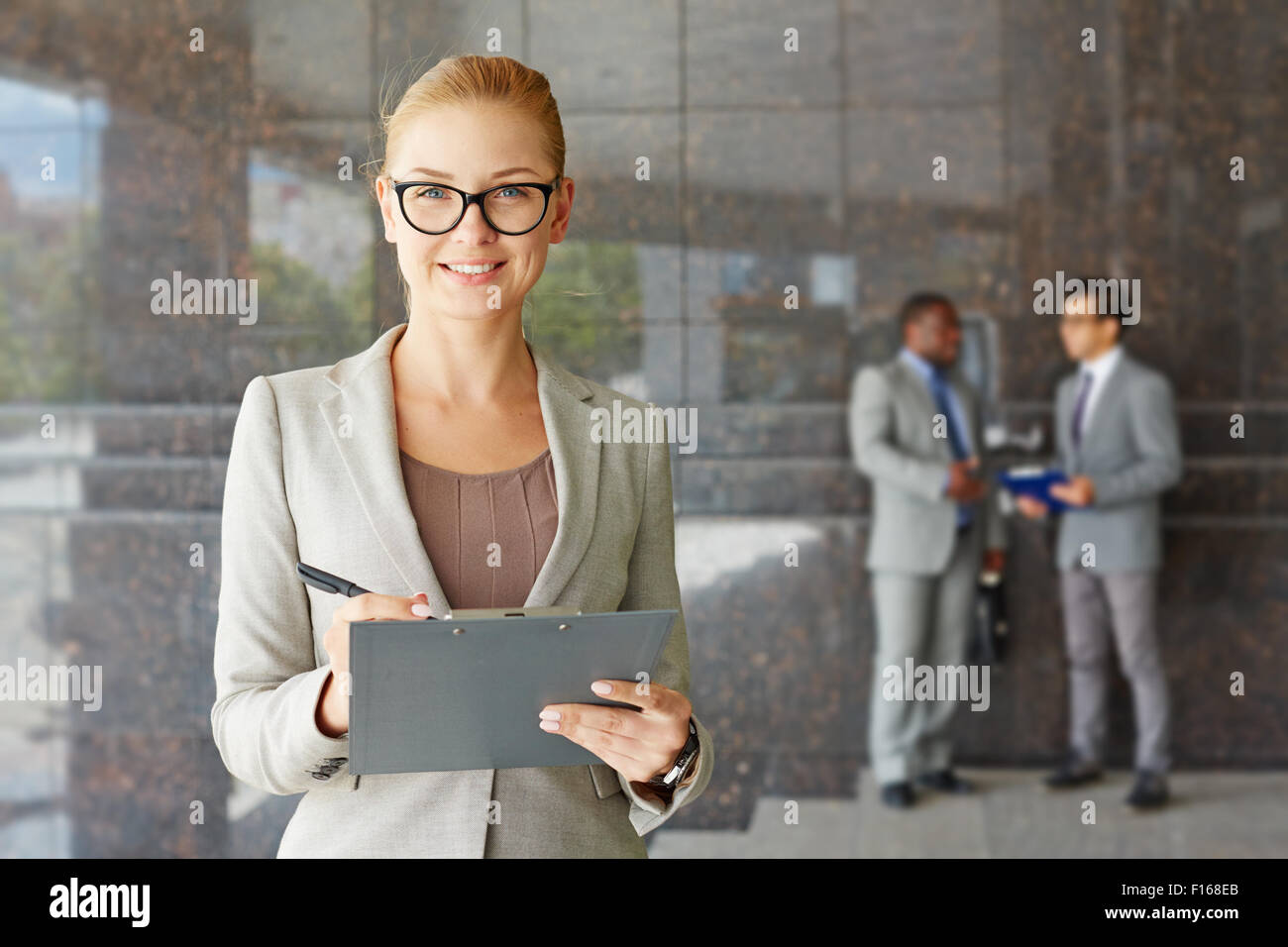 Young seriously looking businesswoman smiling at camera Stock Photo
