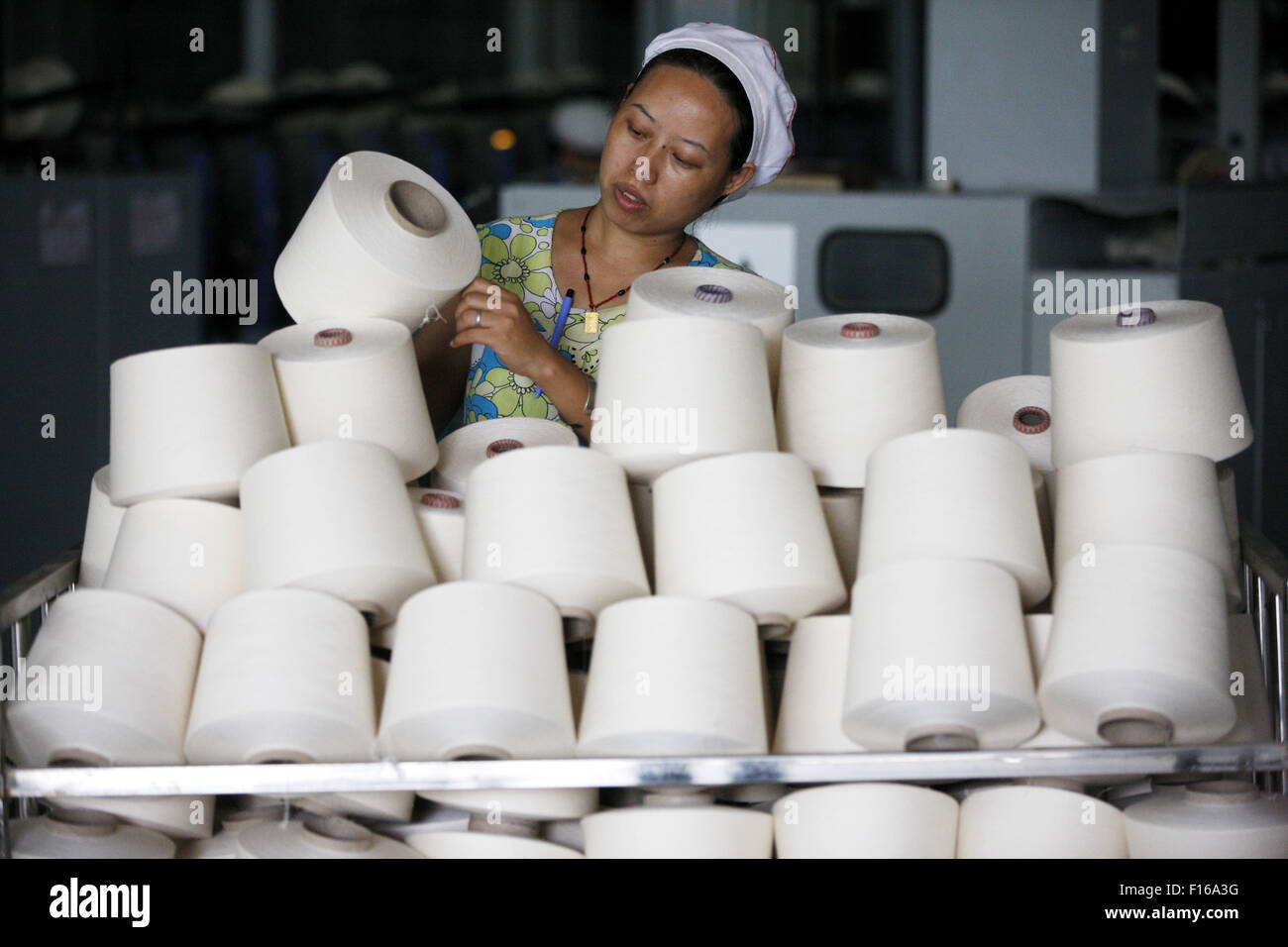 A labour works in a textile factory in Huaibei, Anhui province, China on 28 August 2015. Profits earned by Chinese - Stock Image