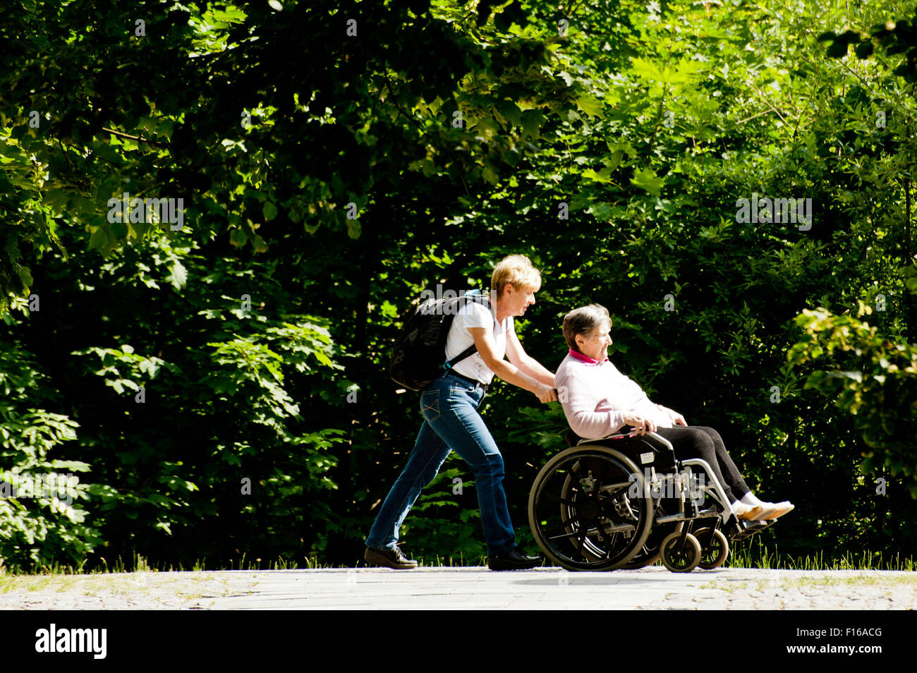 woman pushing an elder disabled woman in wheelchair - Stock Image