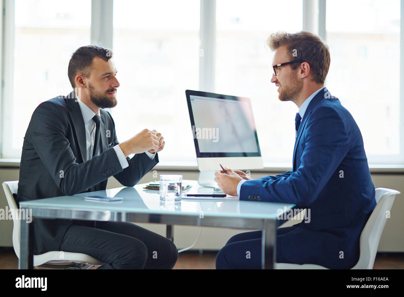 Confident businessmen sitting by table during consultation - Stock Image