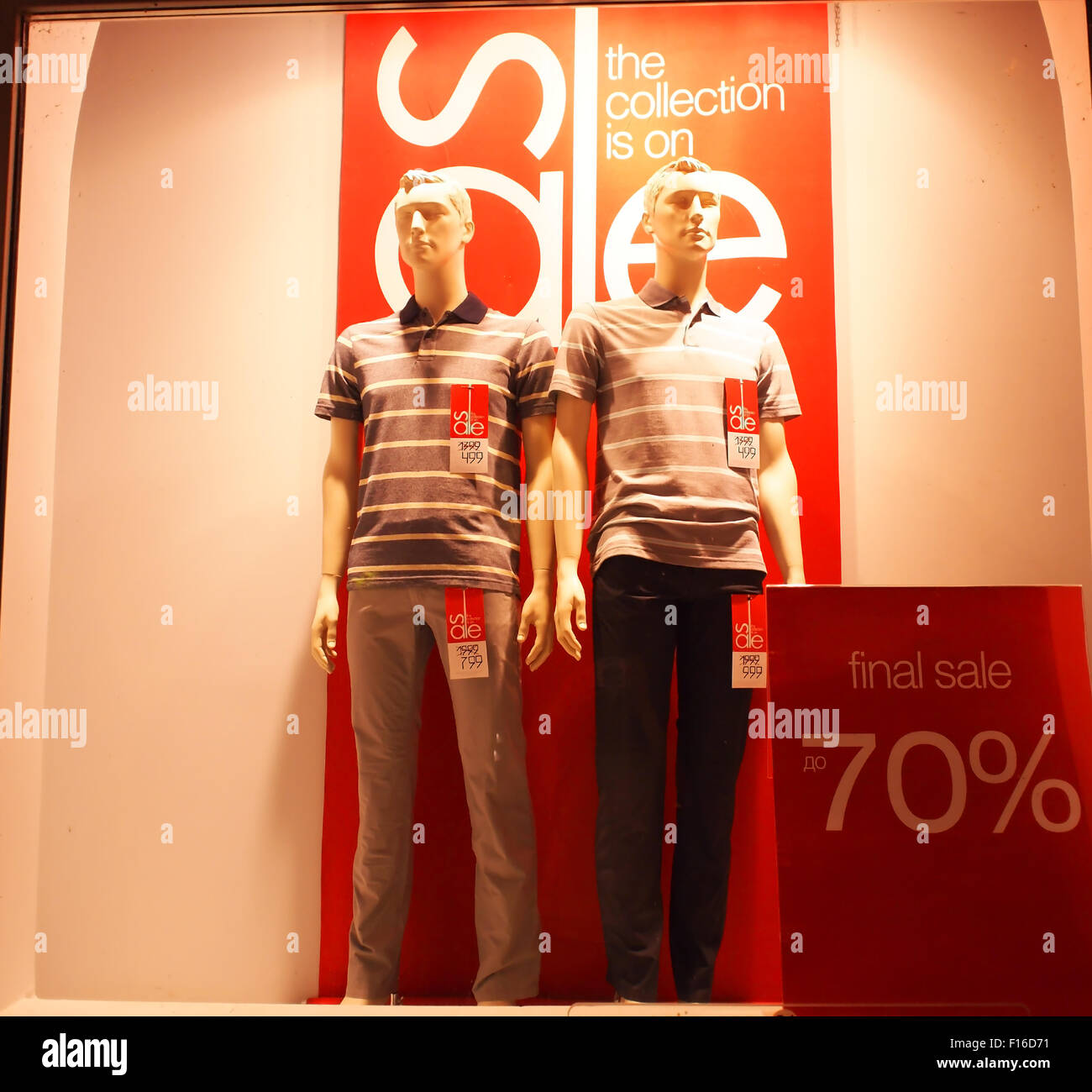 Two male mannequin in a glass case, dressed in typical pants and shirts common. In the showcase it is written - - Stock Image
