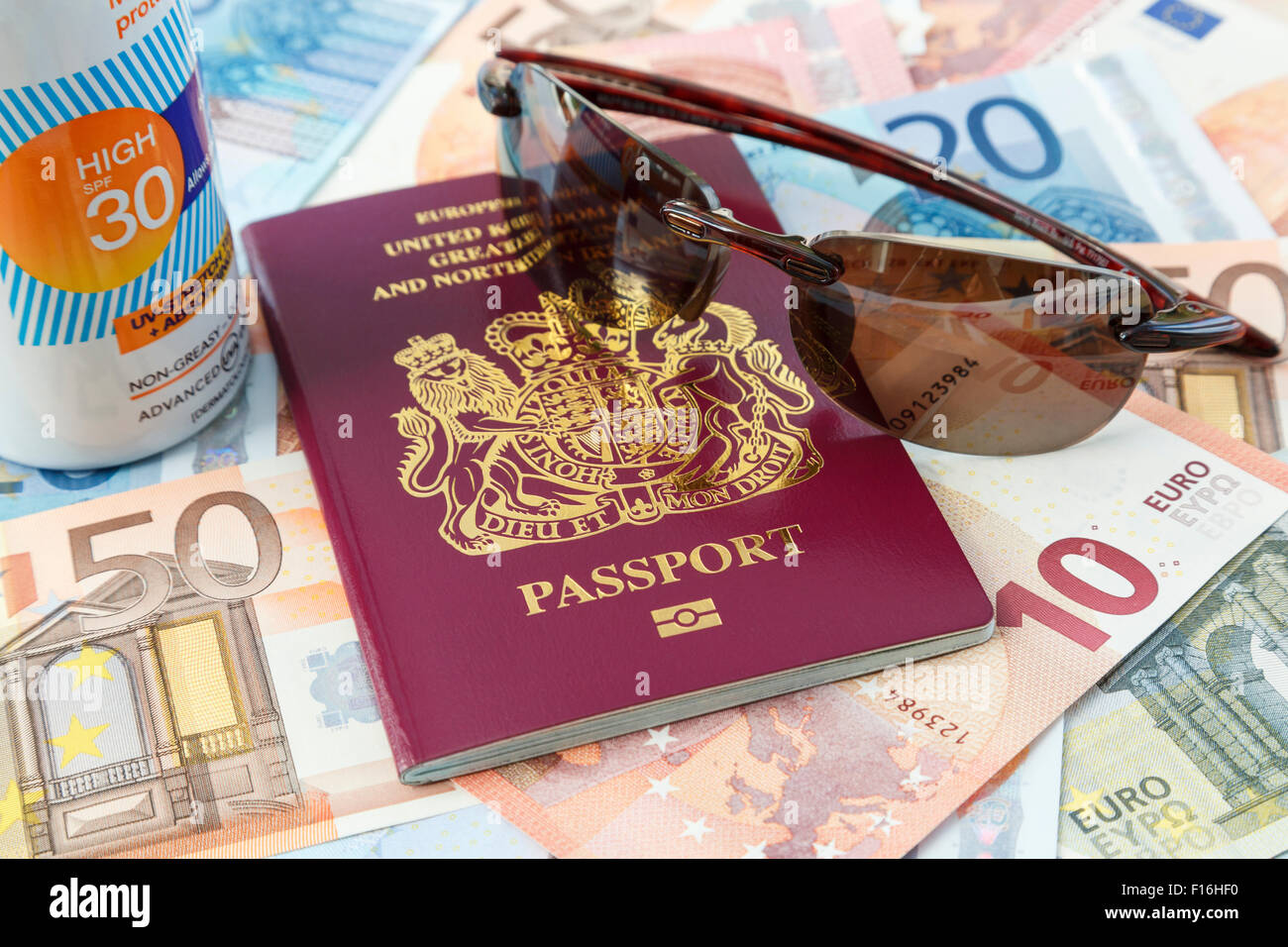 Travel things with British biometric passport Euro currency suncream and sunglasses for travelling to Eurozone countries - Stock Image