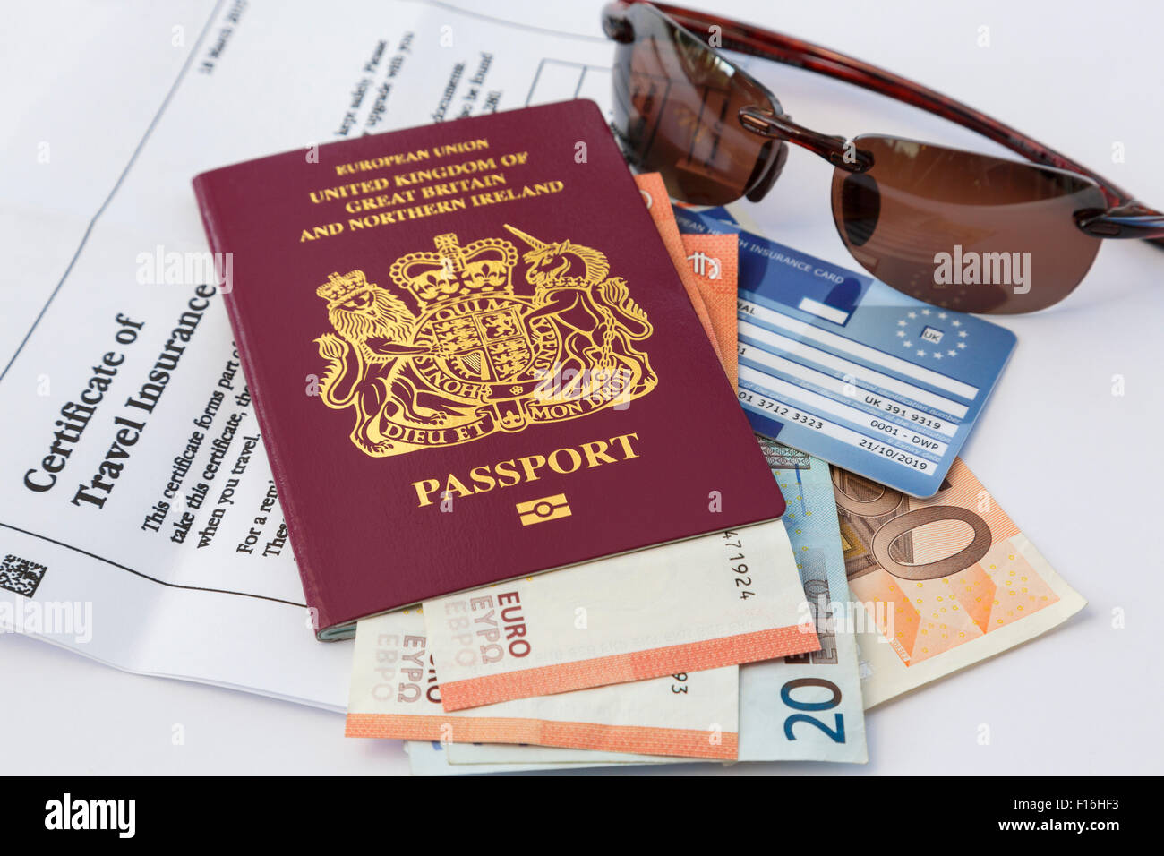 Travel things passport insurance documents and currency money EHIC card and sunglasses for travelling to Eurozone - Stock Image
