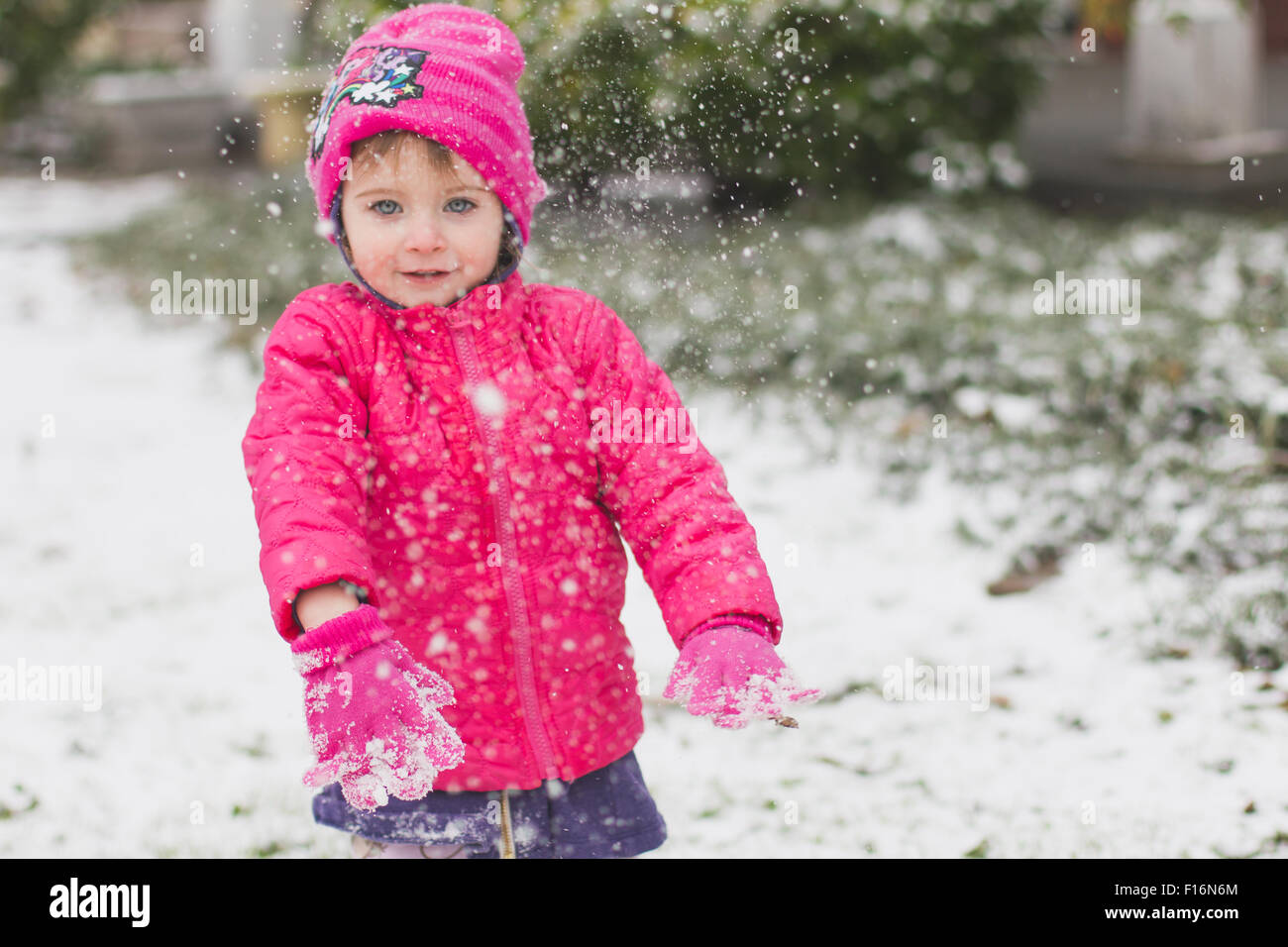 Young toddler girl is throwing snow while wearing a pink coat and hat - Stock Image