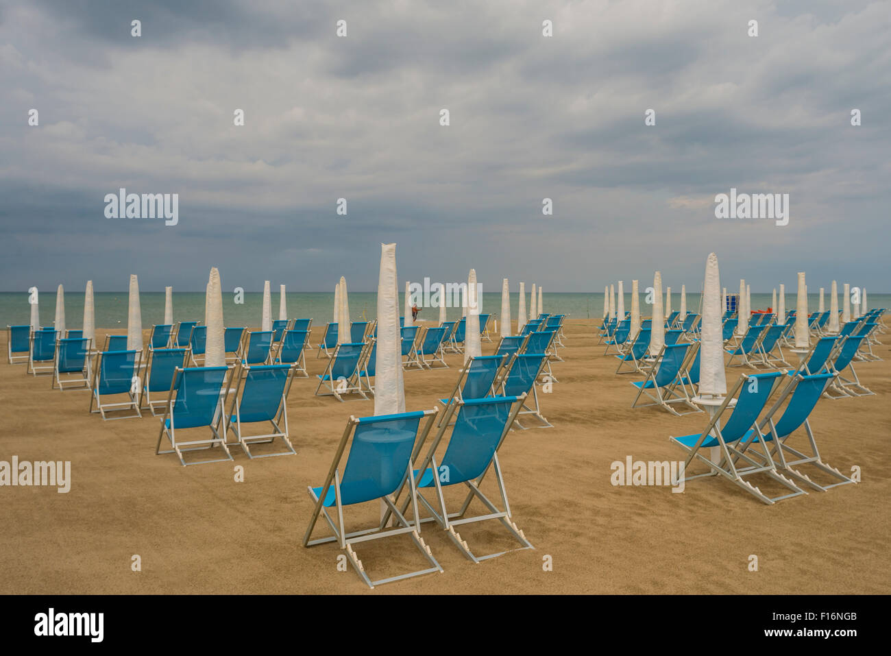 Standing at attention - the army of beach chairs and umbrellas is waiting for the invasion of sun-worshippers - Stock Image