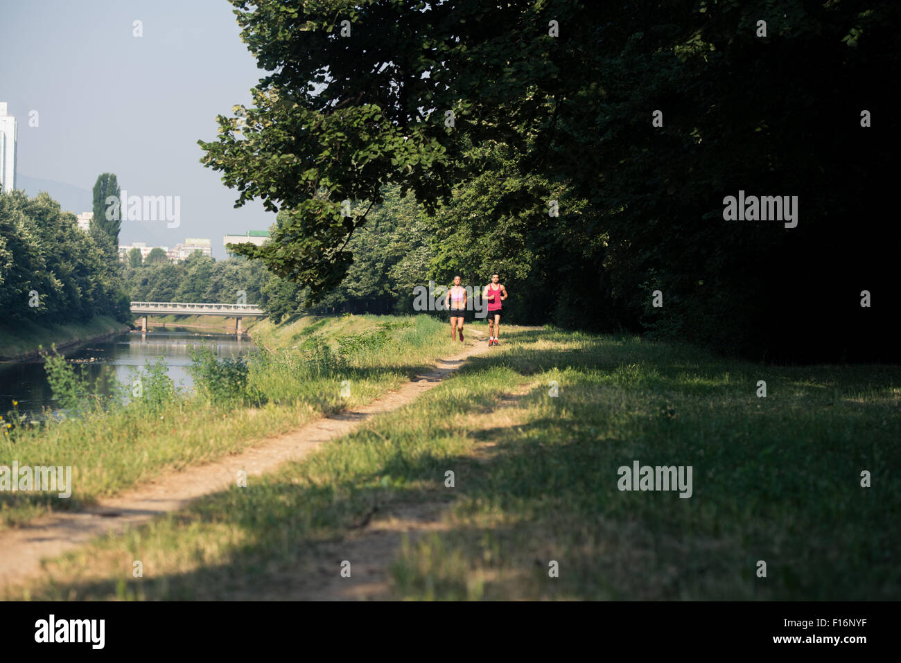 Young Couple Running In Wooded Forest Area - Training And Exercising For Trail Run Marathon Endurance - Fitness - Stock Image