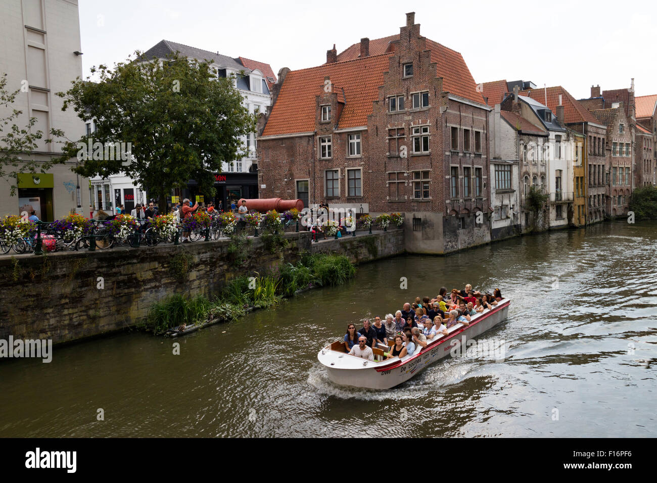 Sightseeing boat with tourists on the river Lye in Ghend, Belgium - Stock Image