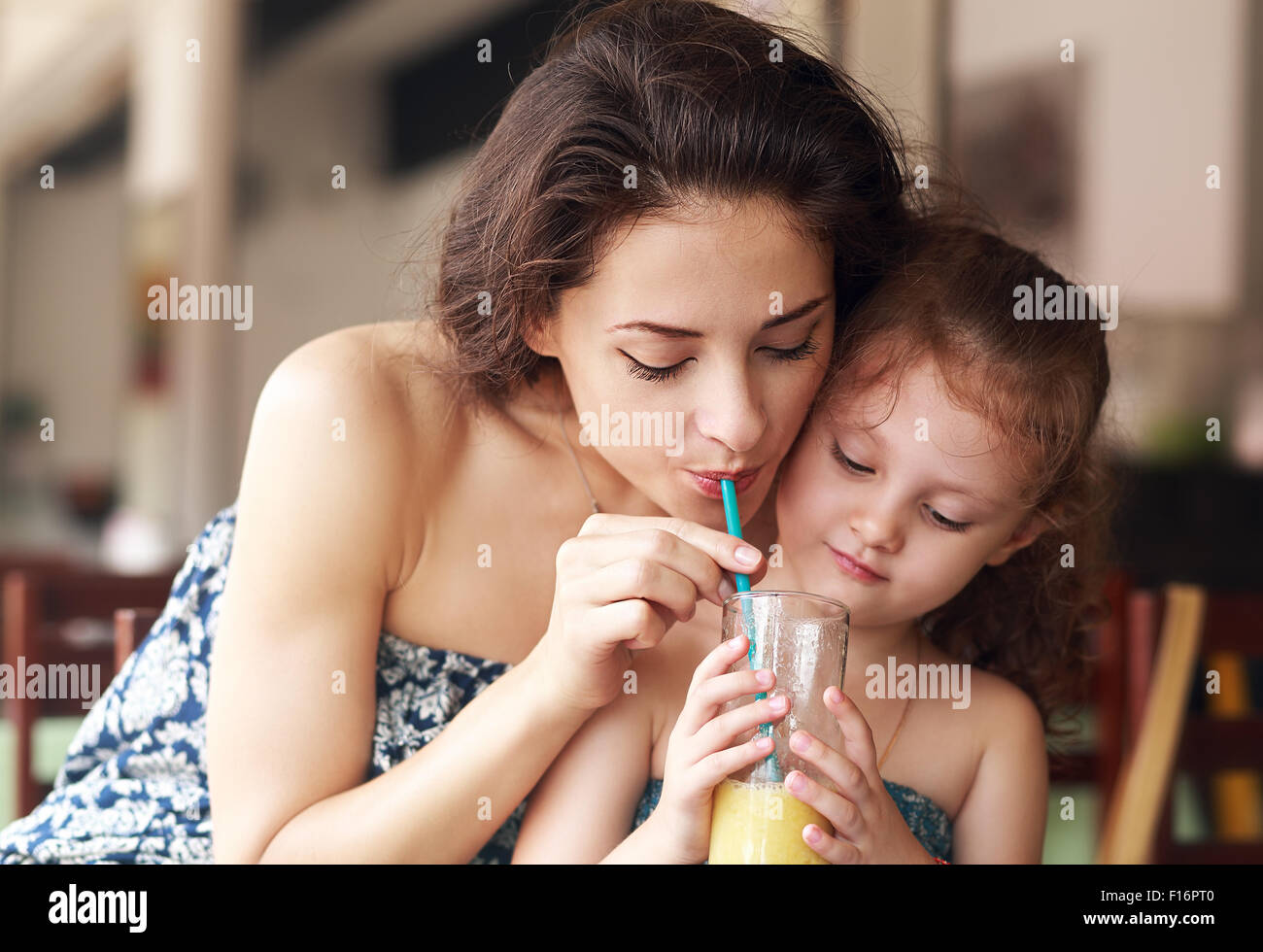 Happy family drinking orange juice and joying together in urban cafe. Closeup natural emotion portrait - Stock Image