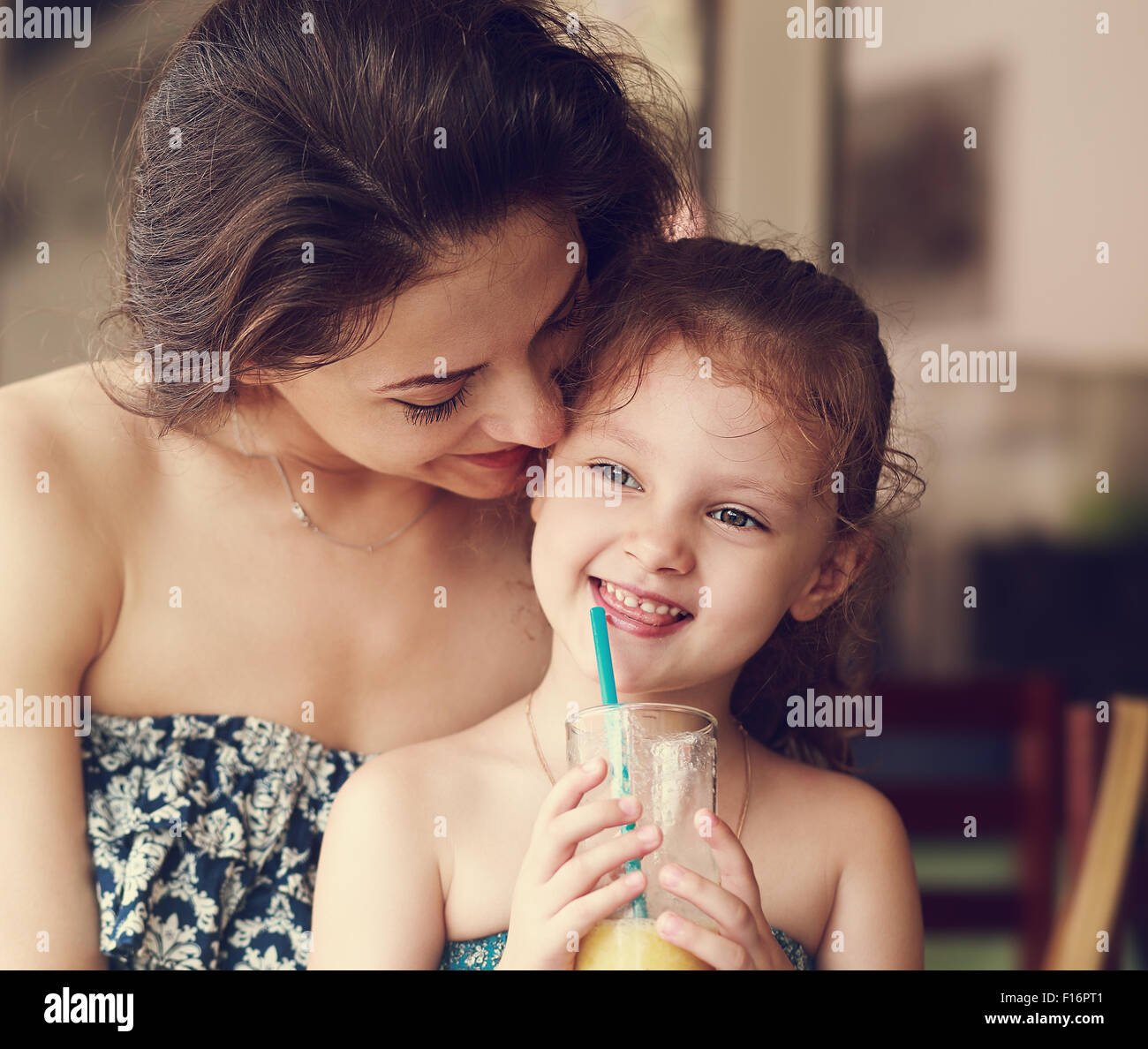 Happy mother looking and hugging her daughter who drinking citrus juice and smiling in restaurant. Closeup portrait - Stock Image