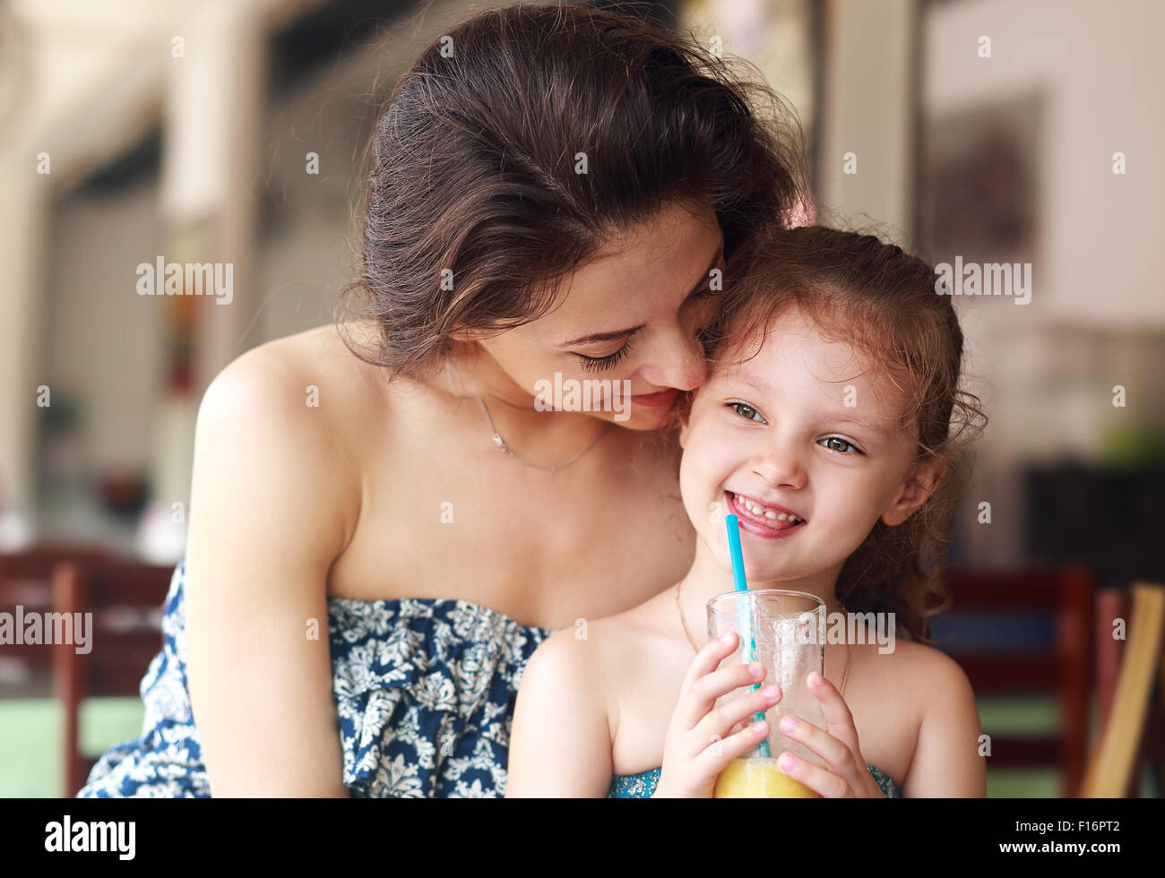 Happy mother looking and hugging her daughter who drinking citrus juice in urban restaurant - Stock Image