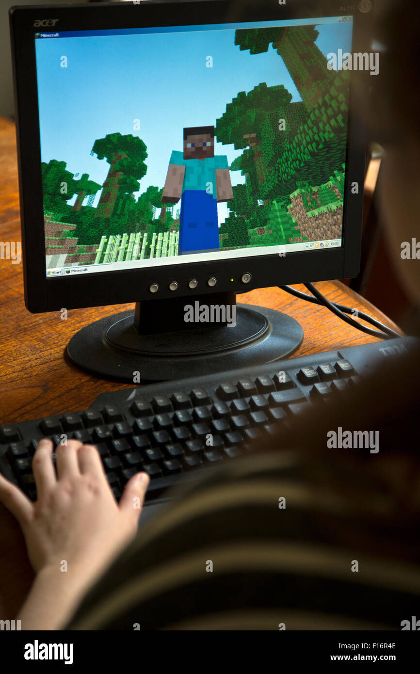 Teenage girl plays the video game Minecraft on a home computer - Stock Image