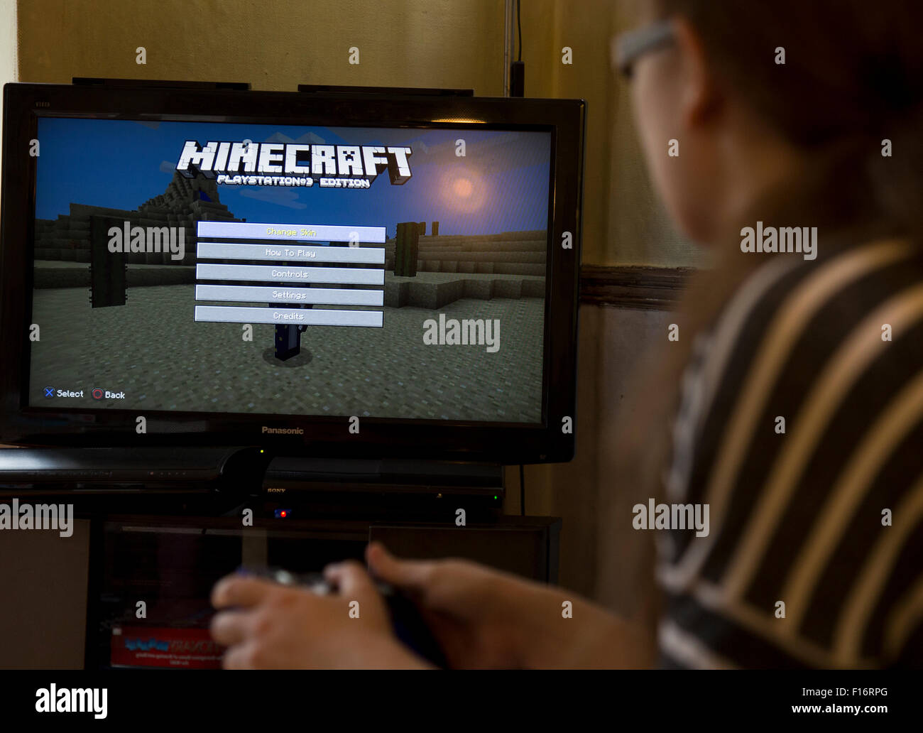 Teenage girl plays the video game Minecraft on a video consol - Stock Image
