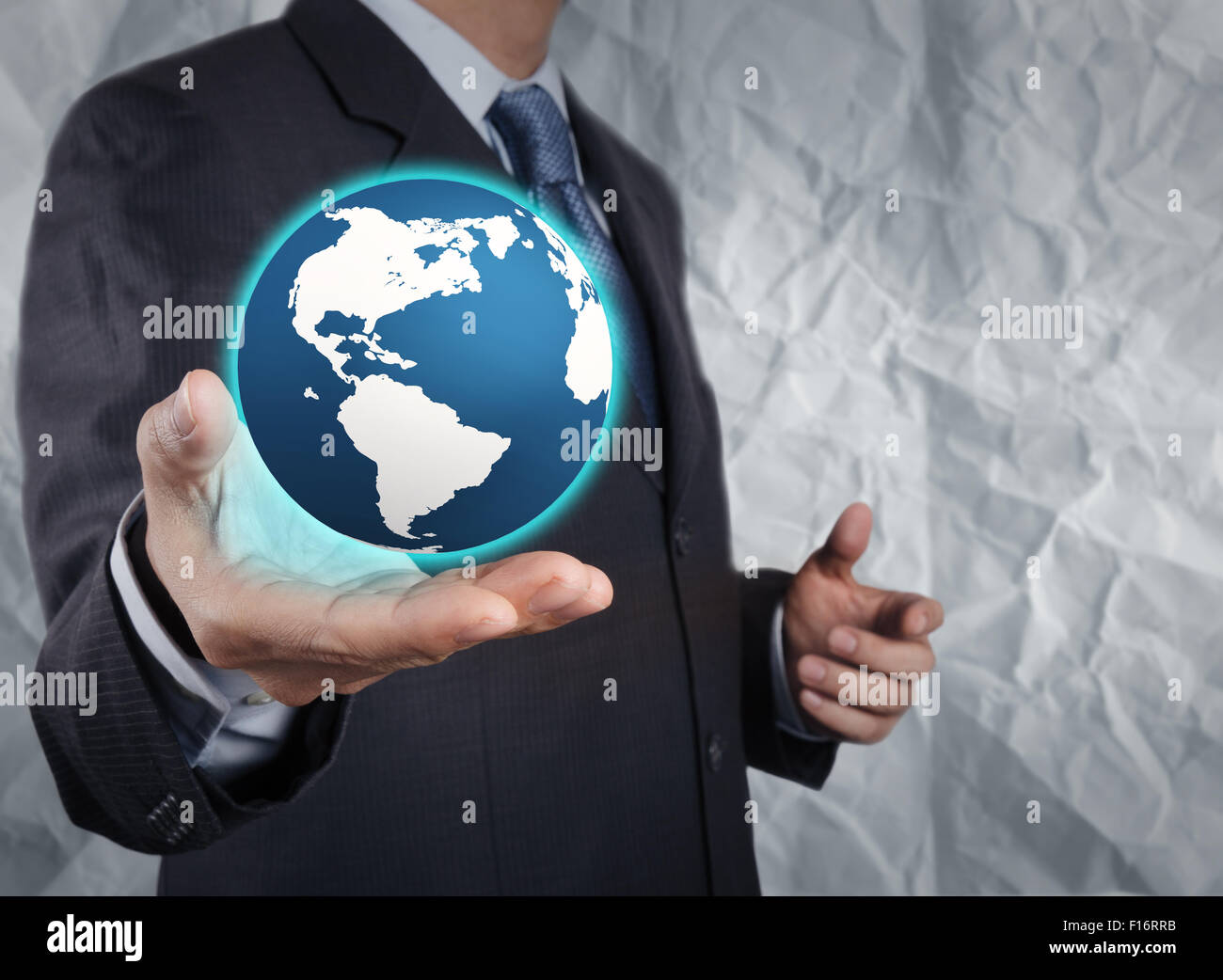 businessman  show the earth with crumpled recycle paper background as concept Stock Photo