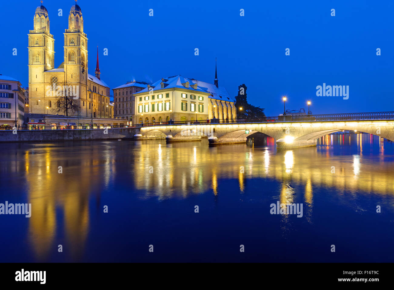 A bridge and the Minster in Zurich in winter at night - Stock Image