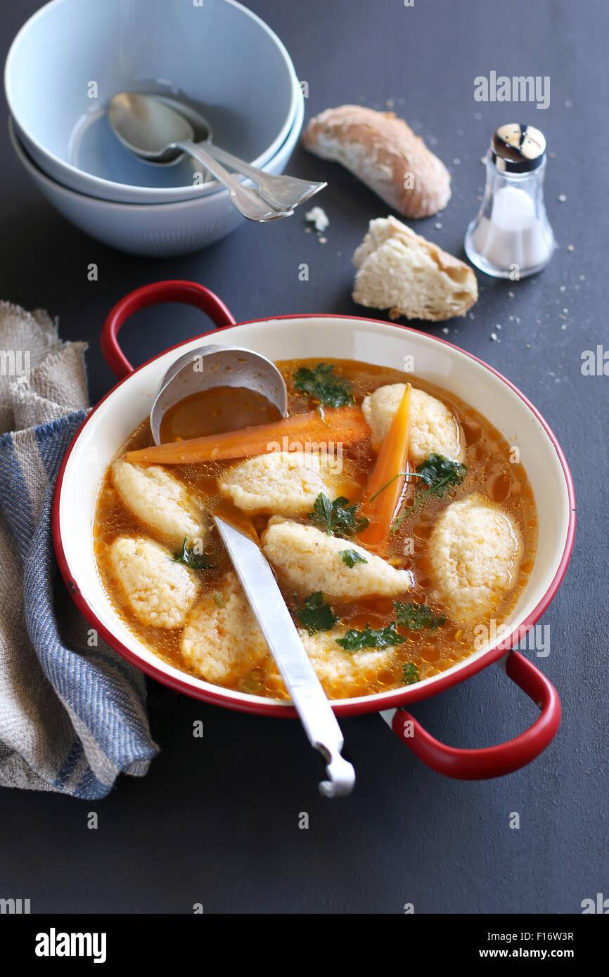 Semolina dumpling soup in an enamel pan - Stock Image