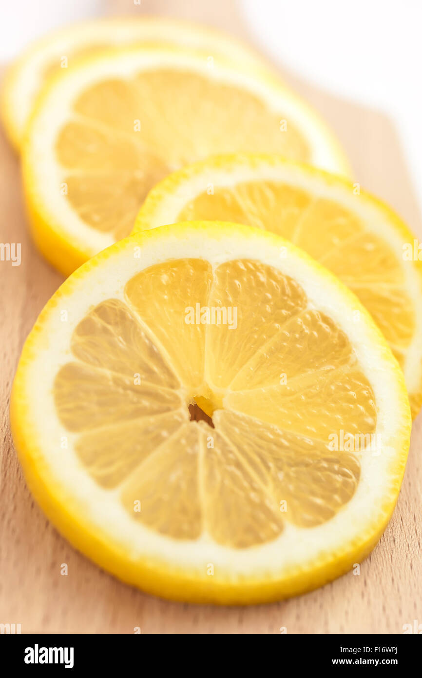 Juicy slices of lemon on a cutting board, closeup - Stock Image