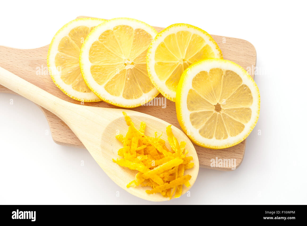 Lemon zest and sliced lemons on a cutting boards, ingredients for a dessert - Stock Image