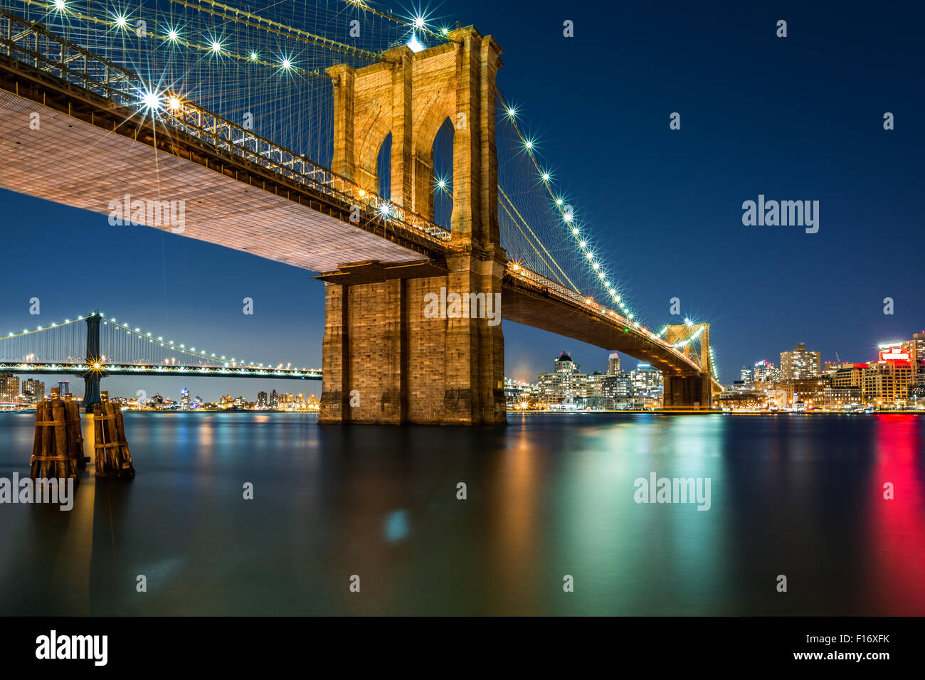 Illuminated Brooklyn Bridge by night as viewed from the Manhattan side - very long exposure for a perfectly smooth - Stock Image