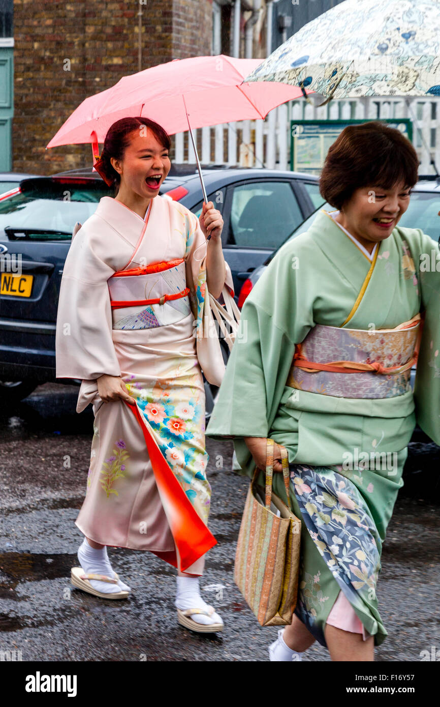 Opera Fans In Kimonos Arrive In The Pouring Rain At Lewes Station En Route To Glyndebourne Opera House, Lewes, Sussex, - Stock Image