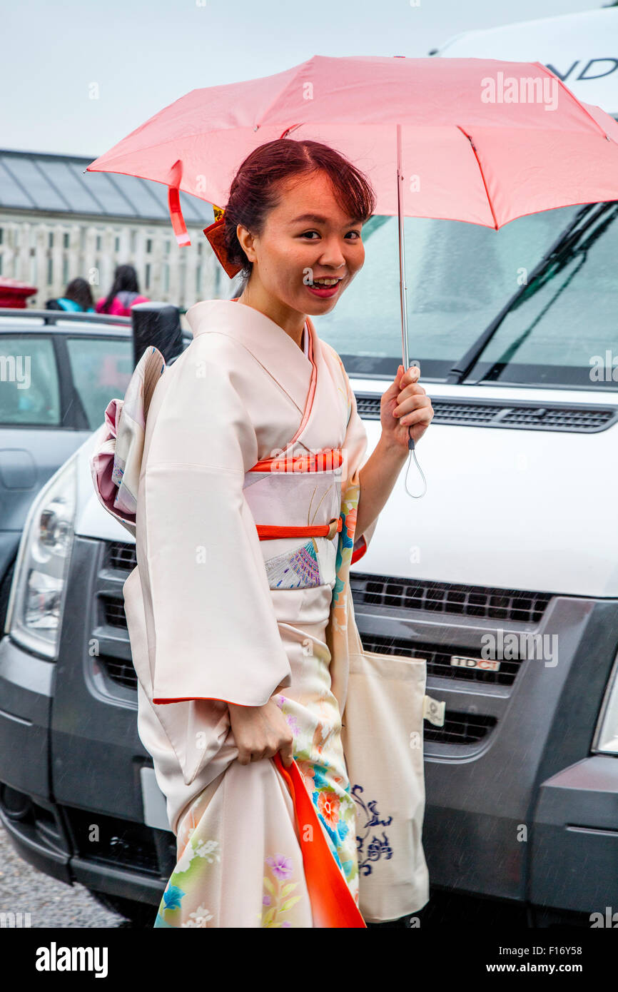 An Opera Fan In A Kimono Arrives In The Pouring Rain At Lewes Station En Route To Glyndebourne Opera House, Lewes, - Stock Image