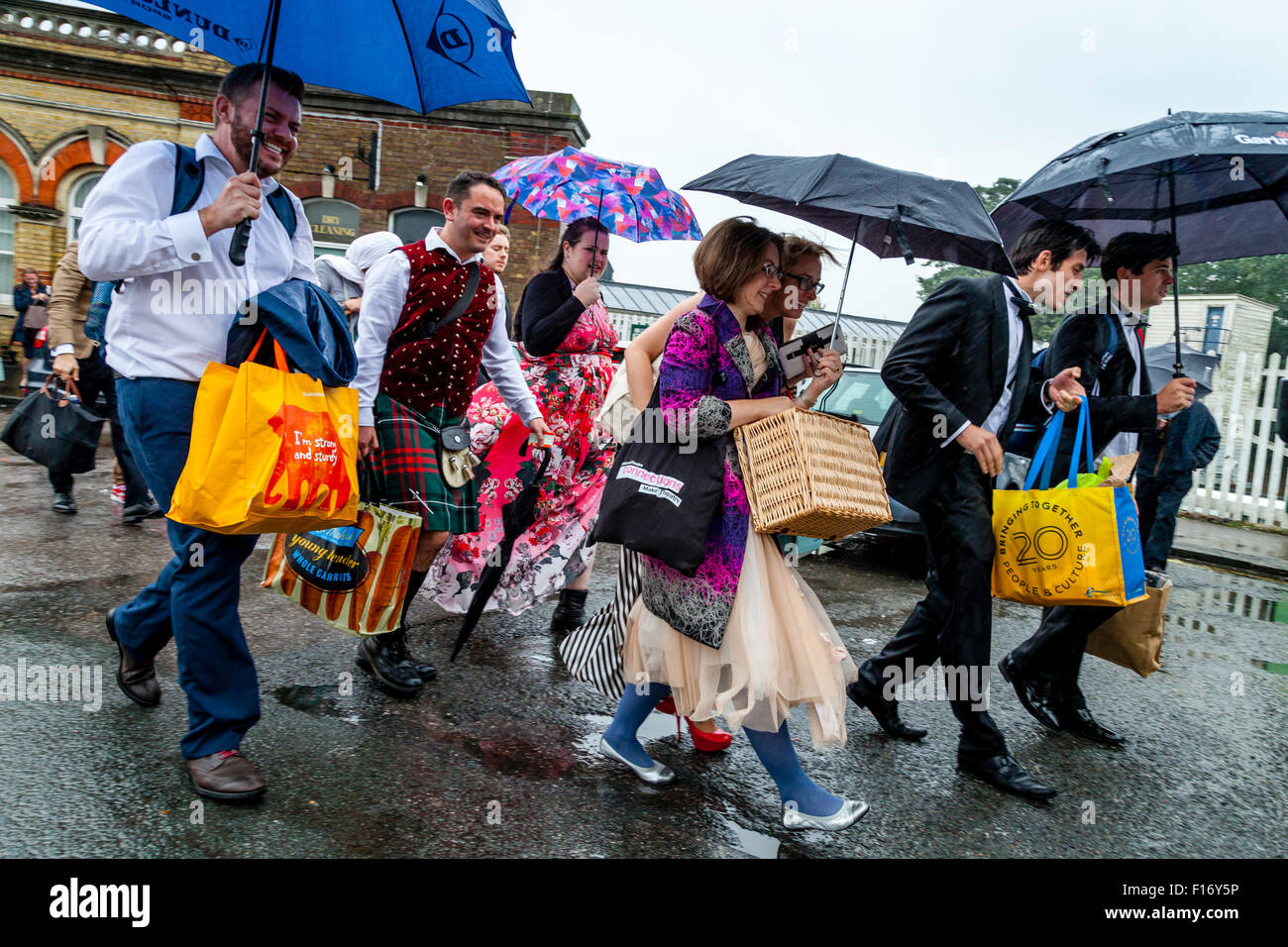 Young Opera Fans Arrive In The Pouring Rain At Lewes Station En Route To Glyndebourne Opera House, Lewes, Sussex, - Stock Image