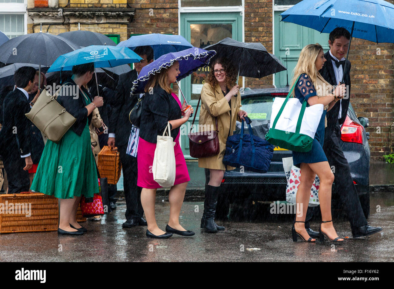 Young Opera Fans Wait In The Pouring Rain At Lewes Station For A Bus Take Them To Glyndebourne Opera House, Lewes, Stock Photo
