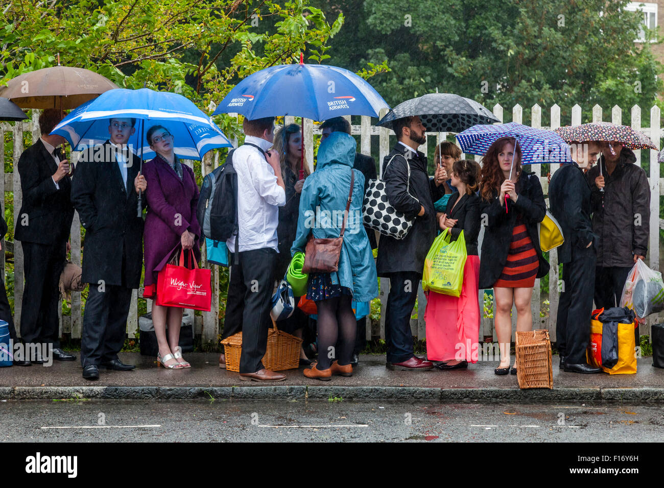 Young Opera Fans Wait In The Pouring Rain At Lewes Station For A Bus Take Them To Glyndebourne Opera House, Lewes, - Stock Image
