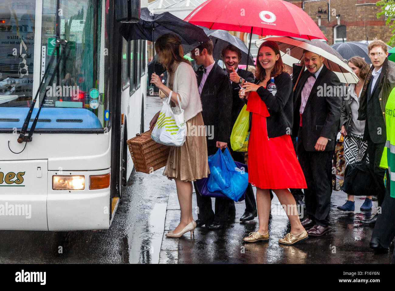 Young Opera Fans Queue To Board A Bus From Lewes To Glyndebourne Opera House To Watch The Opera 'Saul', - Stock Image