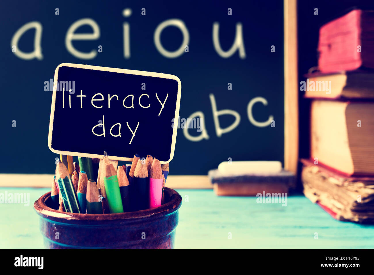 the text literacy day written in a chalkboard, in a retro and rustic classroom, with a filter effect - Stock Image