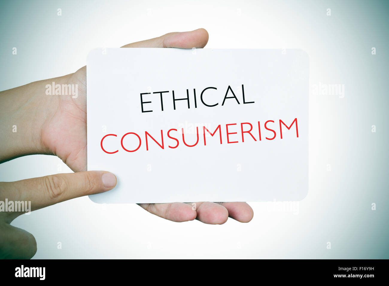 closeup of a young caucasian man pointing his finger at a signboard with the text ethical consumerism, slight vignette - Stock Image