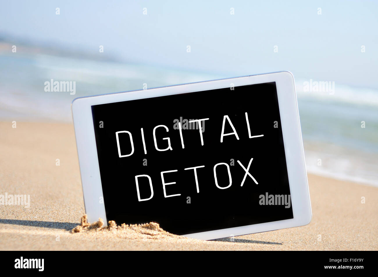 a tablet computer with the text digital detox written in its screen, placed in the sand of a beach - Stock Image