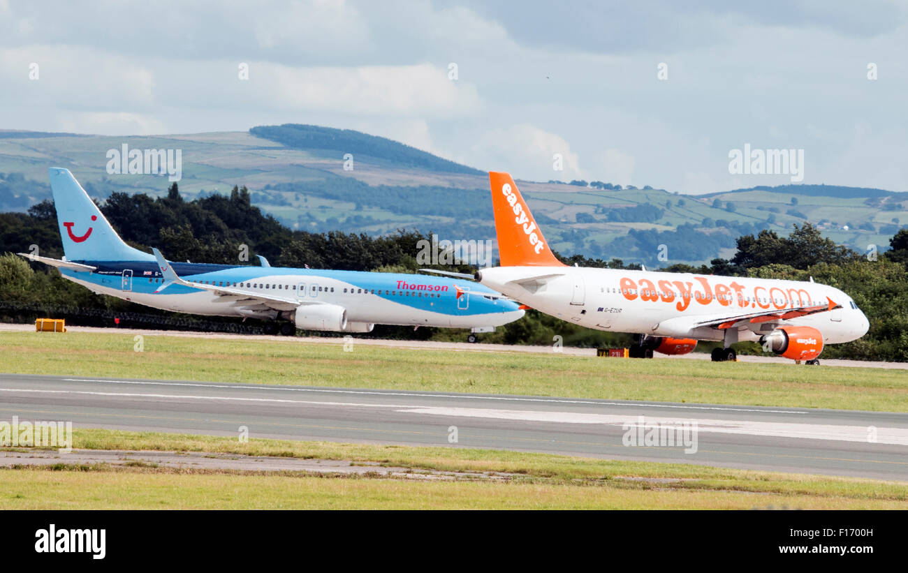 EasyJet, Type: Airbus A320-214 about to take off. Thomson Airways, Type: Boeing 767-304 just landed. - Stock Image