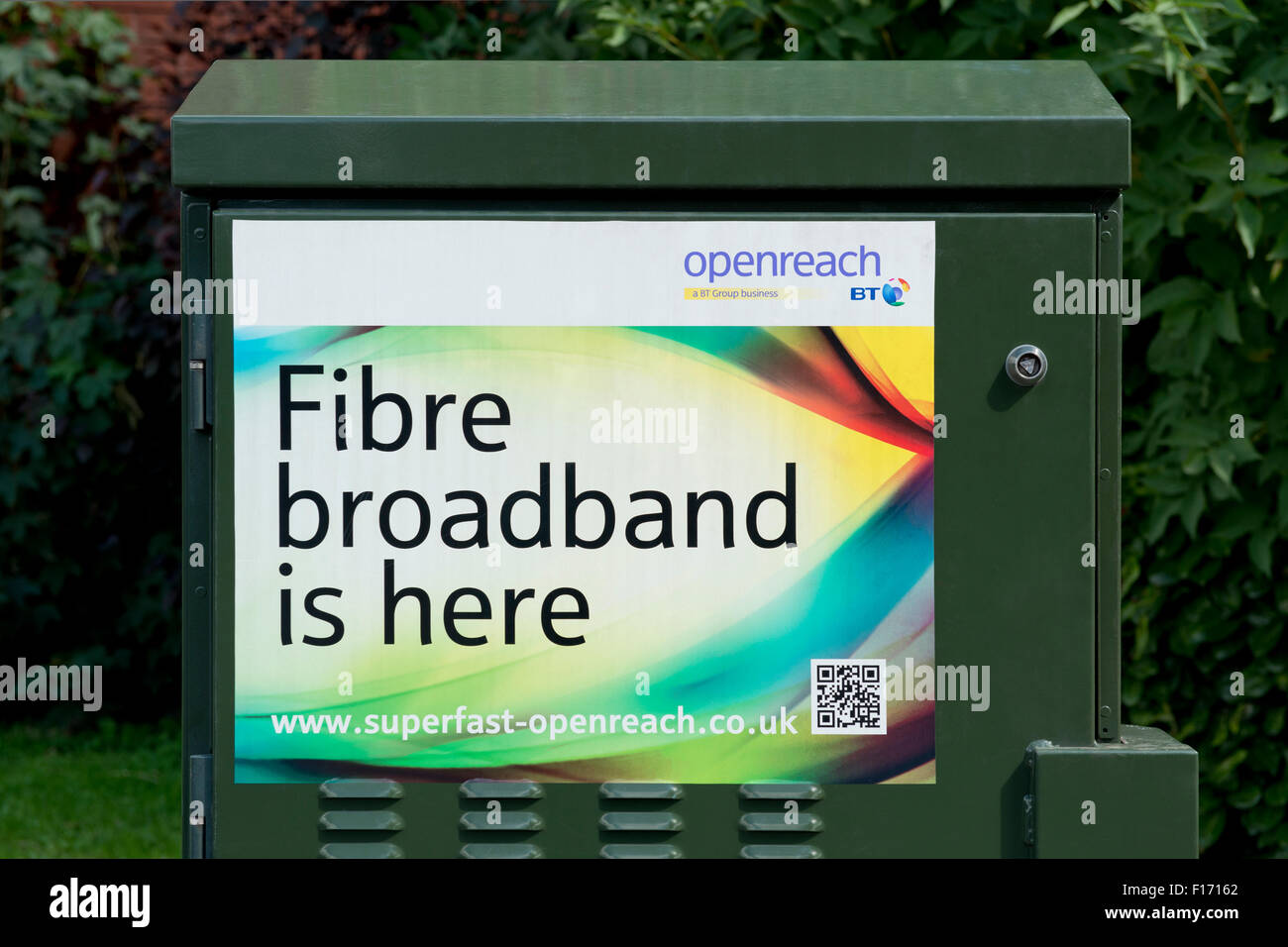 A BT Openreach Fibre Broadband is here sticker on the side of a green engineer's box - Stock Image