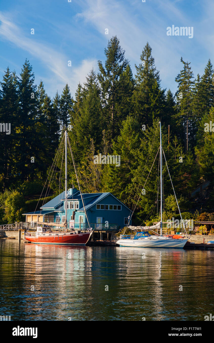 Evening light on sailing vessels docked in a quiet bay of Pender Harbour on the Sunshine Coast of British Columbia, - Stock Image