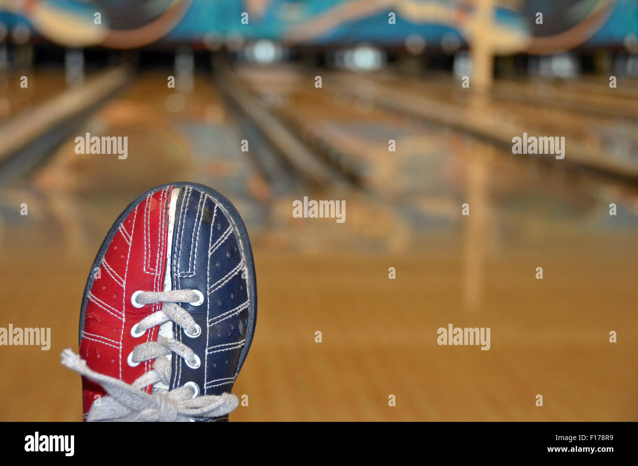 Red and blue bowling shoe with blurred bowling alley background. - Stock Image