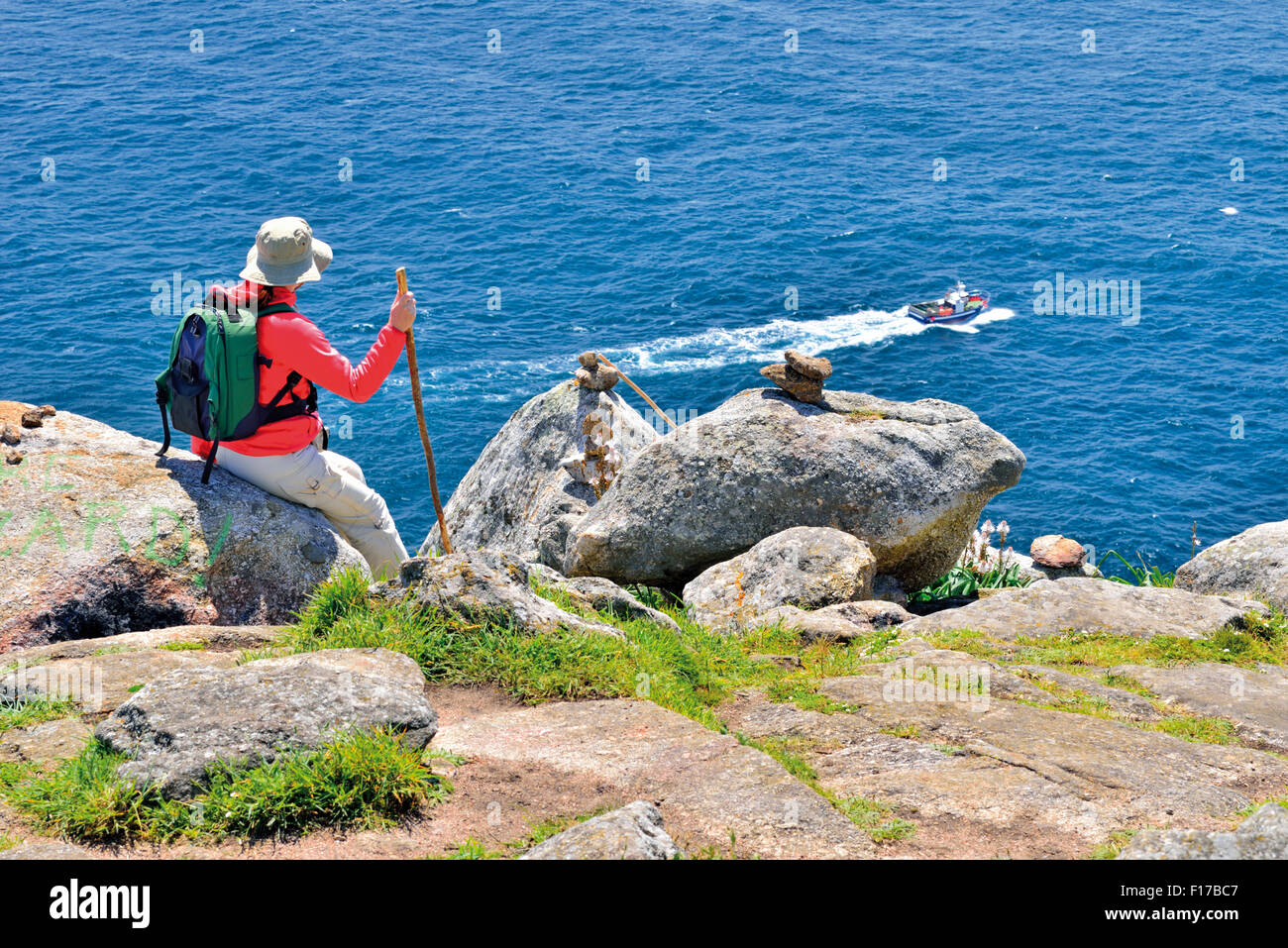 Spain, St. James Way: Pilgrim sitting looking to the ocean at Cape Fisterra - Stock Image