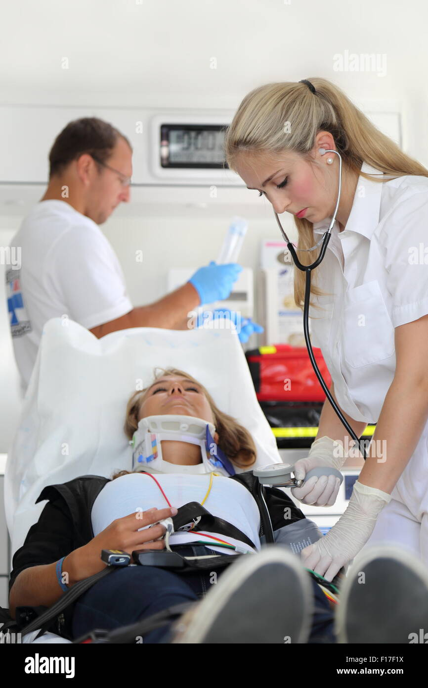 Two emergency room doctors helping a woman with Stifneck - Stock Image